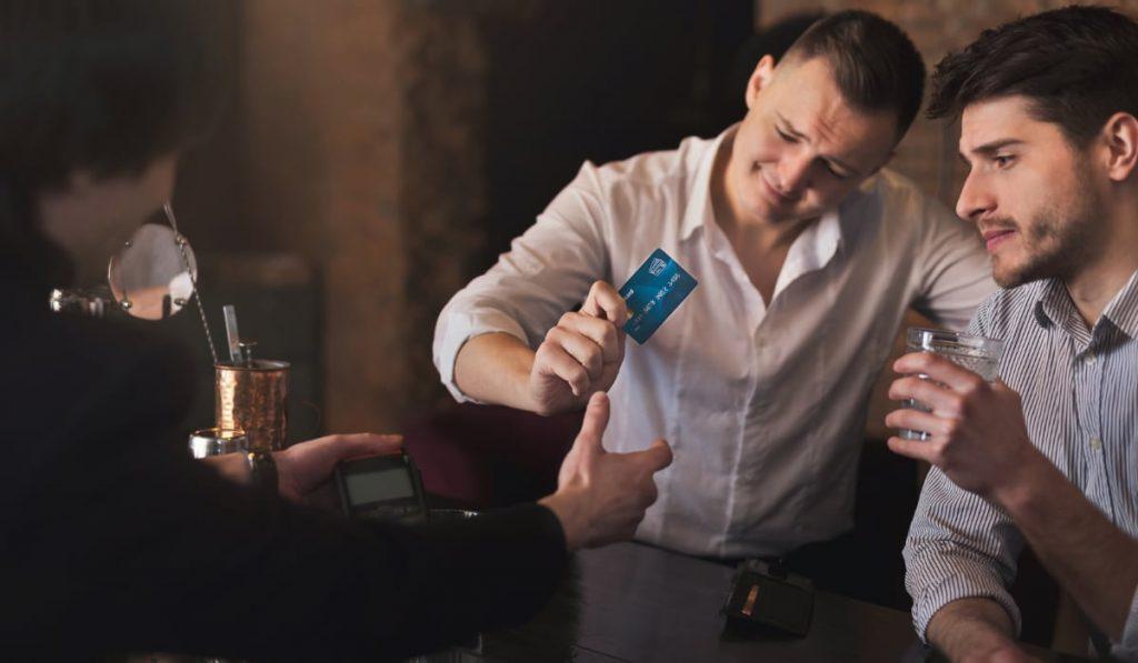 mannen die met een kaart in een bar betalen